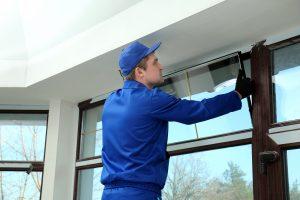 Glazier repairing a window pane in a hotel building